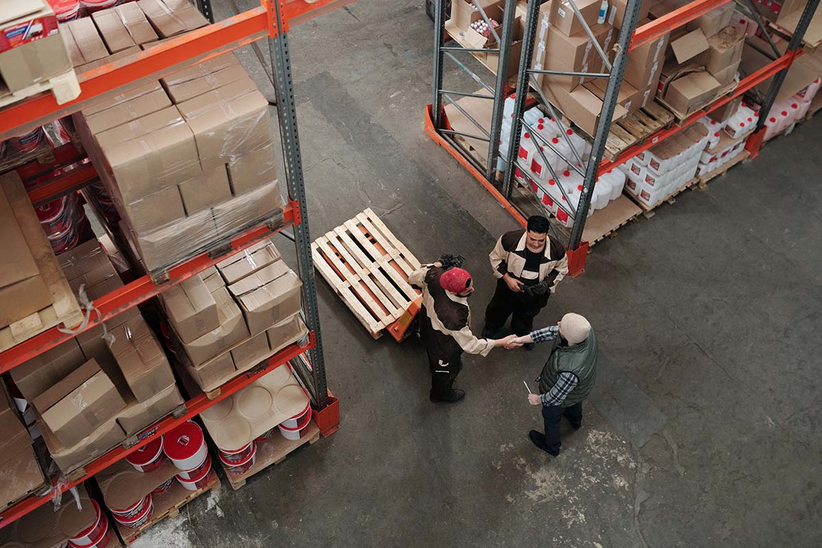 Photo of warehouse with employees shaking hands/